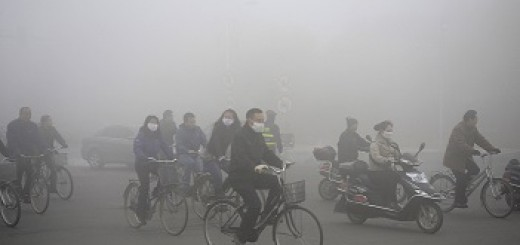 PEOPLE RIDE ALONG A STREET ON A SMOGGY DAY